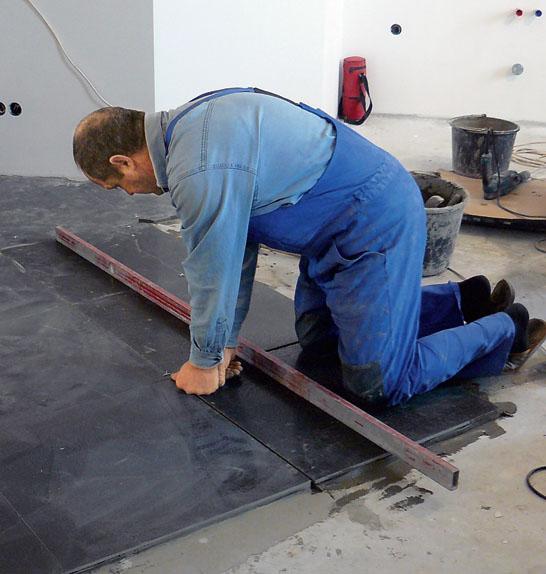 Строительный уровень помогает проверить горизонтальность укладки плитки