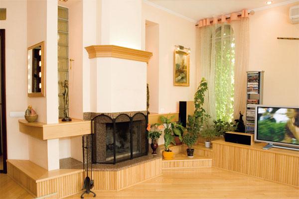 Рядом с камином прекрасно смотрится плазменная панель, а напротив — диванная зона из мягкой кожаной мебели