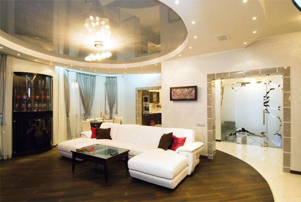 Тема круга в гостиной создана натяжными потолками, встроенными светильниками, повторяющими форму потолка, напольным покрытием
